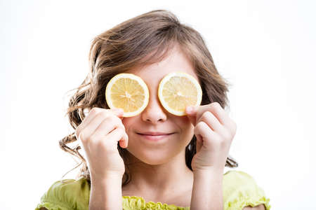 slivers: a little girl showing two lemon slivers over her eyes like lemon-glasses in a funny face