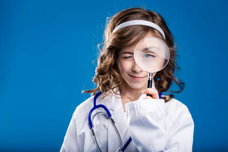 little girl playing as a doctor and looking through a hand lens