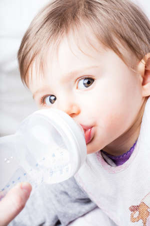 nursing bottle: mother nursing her baby with a baby bottle while this little girl looks at the camera