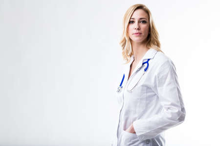 white coat: this beautiful blonde woman on a white coat is a doctor and shes waiting for her patient to tell her whats the problem because shes wellcoming Stock Photo