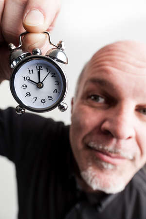 goes: wideangle closeup portrait of a man holding an alarm clock claiming time goes by