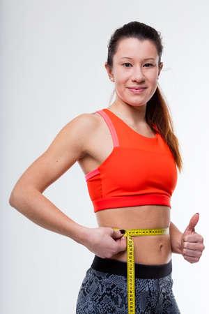 flat stomach: pulgar hacia arriba por una acaba de terminar de trabajar fuera mujer, satisfecho y feliz debido a su vientre plano y su paquete de seis