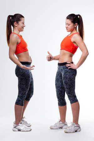 flat stomach: mujer joven que mira su vientre plano perfecto y que muestra los pulgares para arriba
