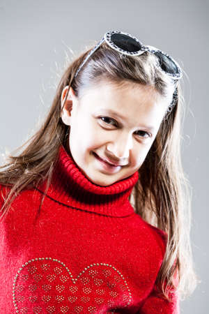 elementary age girls: smiling girl portrait with sunglasses and red sweater Stock Photo