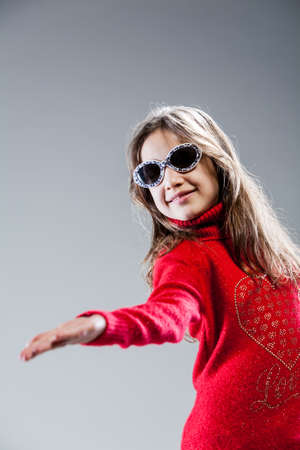 showgirl: girl on a red sweater and sunglasses plays as a fashion model and star Stock Photo