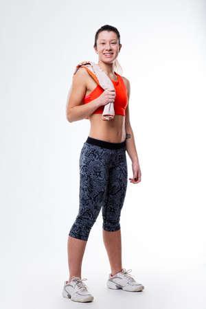 flat stomach: sonriente mujer orgullosa terminado o iniciar su entrenamiento diario de pie con su toalla y su vientre plano y el estómago