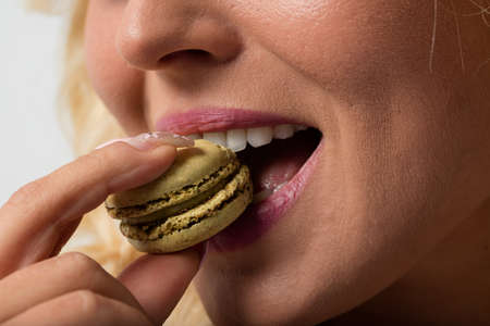 gluttonous: blonde young woman loving to eat a green macaron with witch shes falling in love