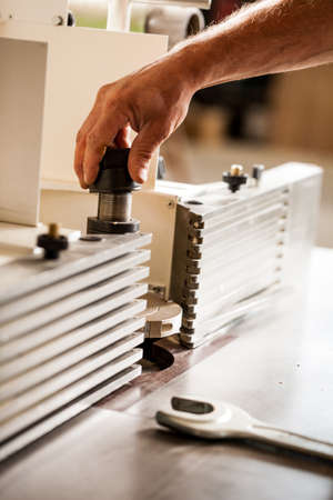 proficient: detail of a hand of a woodworker setting up a milling cutter