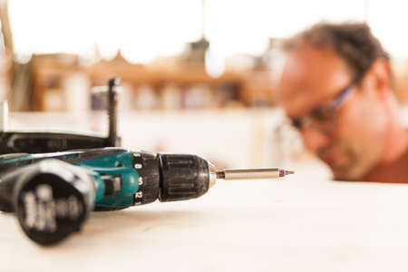 fastener: fastener drive in focus and woodworker on  the background