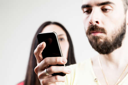 mujer decepcionada: woman disappointed with his man watching a smartphone or texting Foto de archivo