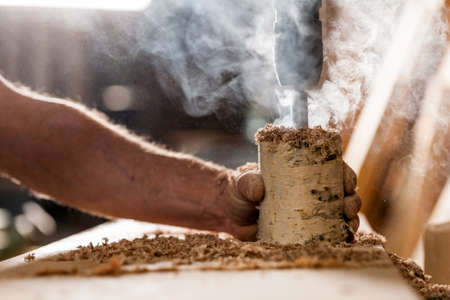 woodworker holding and drilling a log with a hole saw Stock Photo