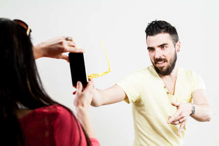 futility: wounded-up couple taking photographs with their smartphones