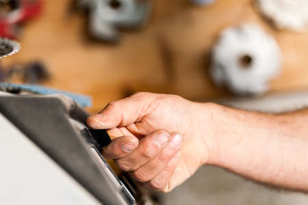 joinery: hand of a woodworker switching on a machine in joinery workshop Stock Photo