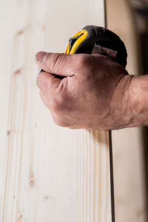 proficient: woodworker hand holding a measuring tape while holding a board