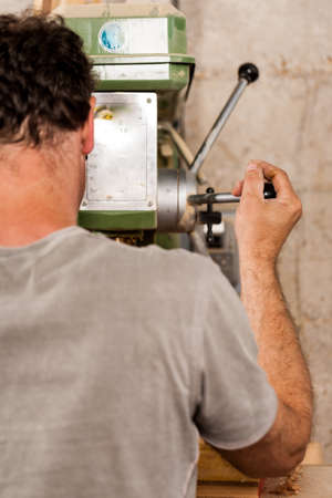 woodworker: woodworker drilling a plank with machinery in his workshop Stock Photo