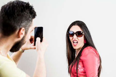 boor: wounded-up couple taking photographs with their smartphones
