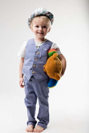 romper: little baby on romper suit with hat hugging his teddy bear Stock Photo