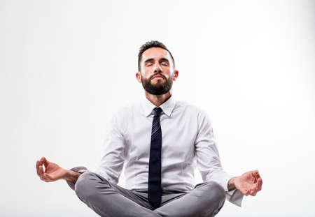 relaxed business man in meditation pose on white background