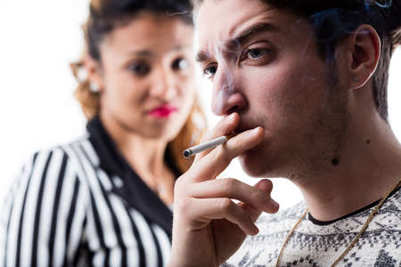 stench: man smoking and woman very disgusted by that stench