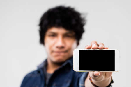 mulatto: blank screen of a smartphone (copyspace) shown to you by a robust mulatto guy
