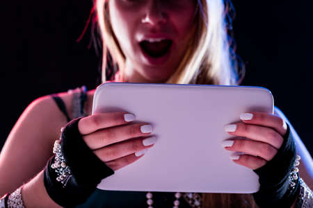 live event: young woman living a live event online using some internet connection or service via her digital tablet and feeling as like as if she was really there Stock Photo