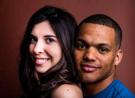 sexo pareja joven: pareja interracial sonriente retrato sobre fondo marr�n