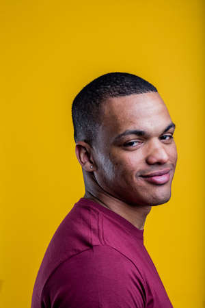 skeptical: portrait of skeptical afro-american man on yellow background wearing a purple t-shirt
