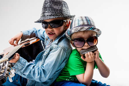 two little children playing and singing some music pretending to be blues or rock stars