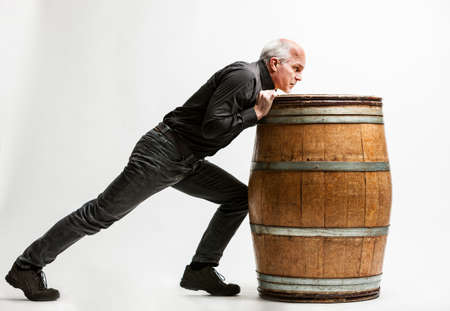 resolute artisan pushing a wine barrel Stock Photo