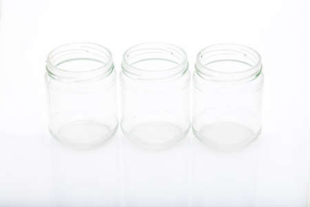 reflective: three little glass vases on a reflective white surface Stock Photo