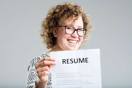 looking for work: curly woman on a neutral background showing her resume Stock Photo