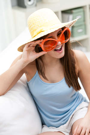 sunhat: Fun trendy young woman in orange sunglasses and a straw sunhat laughing as she peers over the top of the frames at the camera