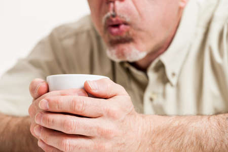 Cropped head and shoulders of mature man blowing into little white teacup in hands