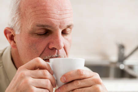 Close up on single bearded mature man with eyes closed and sleepy expression sipping coffee from little white tea cup