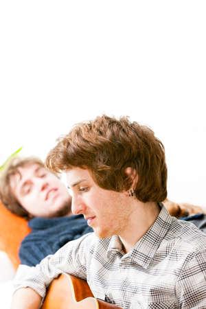 music lyrics: Apuesto joven tocando la guitarra por un amigo que está descansando en un sofá junto a él, cerca cabeza y hombros perfil Foto de archivo