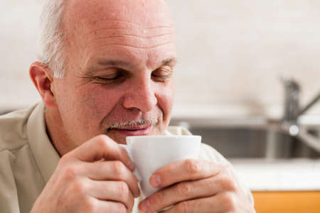 contentment: Close up on single handsome bearded mature man with eyes closed and pleased expression sipping coffee from little white tea cup