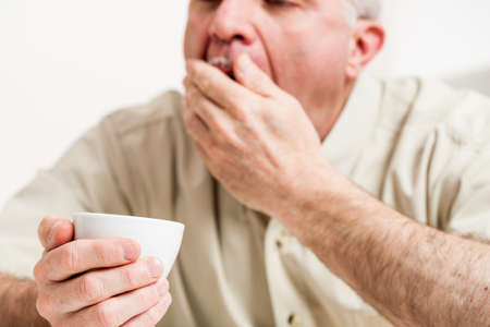 Cropped head and shoulders of yawning mature man with little white teacup in hand