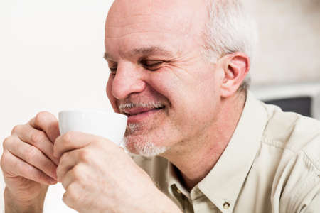 man with a goatee: Close up on single handsome bearded mature man with eyes closed and satisfied smile sipping coffee from little white tea cup
