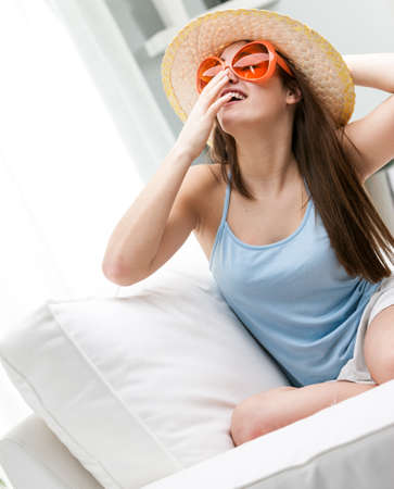 sunhat: Trendy young woman in a sunhat and colorful orange sunglasses sitting on a sofa in a high key white room laughing as she tilts her head back