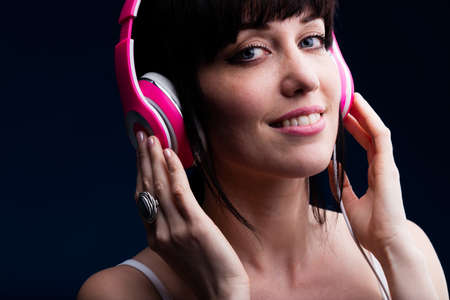 sleeveless top: Close up on single grinning young adult female in sleeveless top using headphones