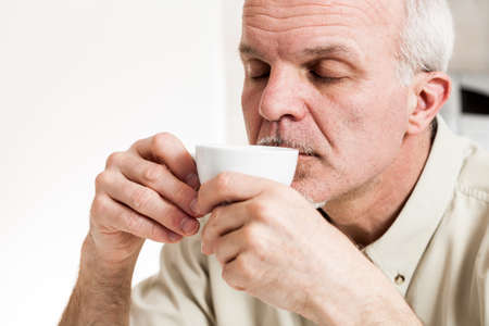 Close up on single handsome bearded mature man with eyes closed sipping coffee from little white tea cup