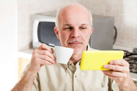 Serious handsome bearded mature man with balding head and buttoned shirt holding yellow digital device and coffee mug while seated in front of microwave oven in kitchen