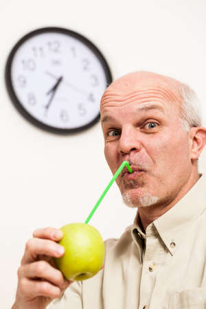 balding: Single handsome bearded mature man with balding head and buttoned shirt pretending to sip juice with straw from whole green apple