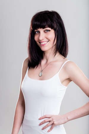 tight fitting: Happy young woman in dark hair, tight fitting sleeveless shirt and hand on hip over gray background Stock Photo