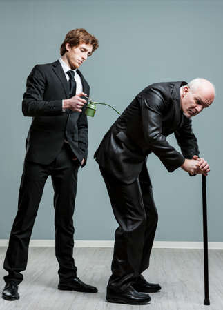 retiring: Generations concept of old and young men with a young businessman standing behind a pensioner using a stick applying oil to his back from an oil can Stock Photo