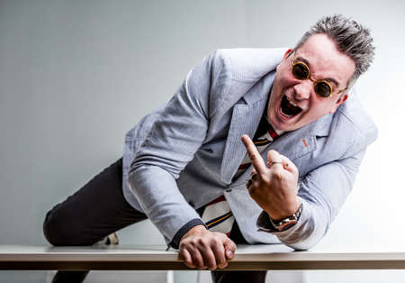 angry crazy businessman showing middle finger and climbing over a desktop to reach you
