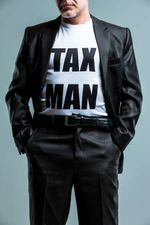 sadistic: Stern man wearing a Tax Man t-shirt standing with his hands in his pocket and suit jacket unbuttoned in a close up cropped three-quarter view Stock Photo