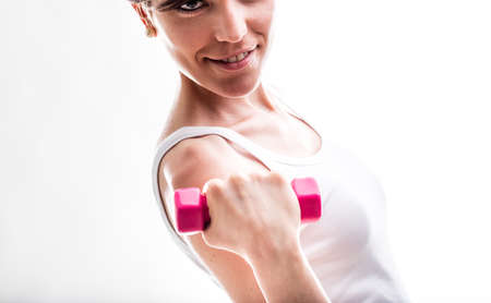 flexed: Fit smiling woman lifting weights holding a pink dumbbell in her flexed hand as she smiles at the camera, close up cropped view Stock Photo