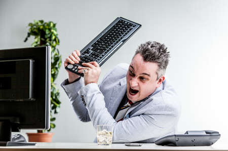 office worker destroying his computer by smashing the keyboard over the screen Stock Photo