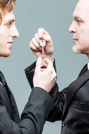 Concept of a generations business turnover with a solemn senior businessman handing over a key to a smiling younger man in a close up view of their hands and faces Archivio Fotografico